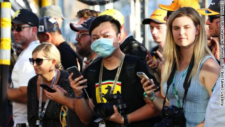 A fan wears a protective mask while standing in the pitlane during previews ahead of the F1 Grand Prix in Australia.