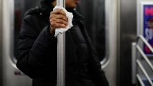 A subway customer uses a tissue to protect her hand while holding onto a pole  Thursday, March 19, in New York City.