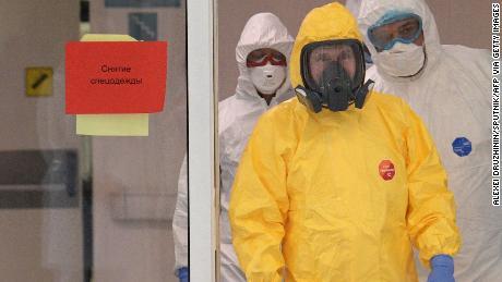Russian President Vladimir Putin visits a hospital in Kommunarka in protective gear.