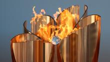 The Olympic cauldron is lit during the 'Flame of Recovery' special exhibition at Aquamarine Park a day after the postponement of the Tokyo 2020 Olympic and Paralympic Games.