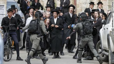Israeli security forces arrest an ultra-Orthodox Jewish man as they close a synagogue in Jerusalem on Monday.