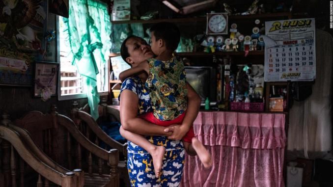 April Abrias hugs her son, Yohan, inside their home after she has disinfected and changed her clothes.