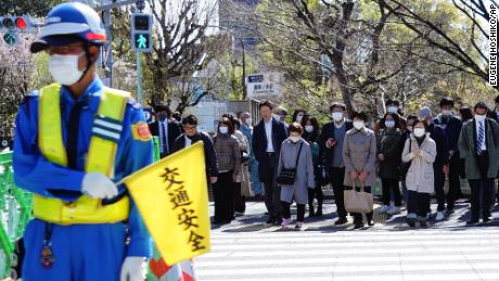 People wearing a protective face mask wait at a pedestrian crossing Thursday, April 2, 2020, in Tokyo.