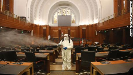 Sanitary workers disinfect the desks and chairs of the Lebanese Parliament on March 10.