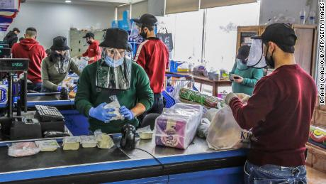 Employees work while wearing protective face shields and gloves at a store in the northern Lebanese city of Batroun on March 23.