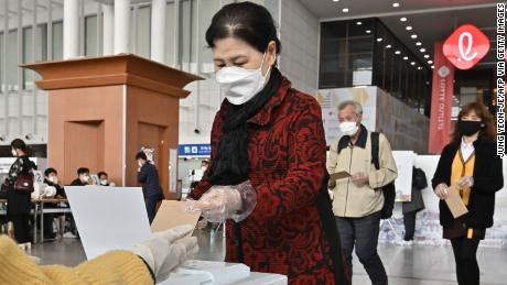 A South Korean woman casts a ballot during early voting at a polling station in Seoul on April 10.