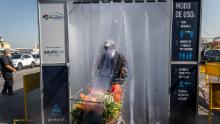 A person wearing a protective mask pushes a grocery cart through a decontamination chamber at the central fruit and vegetable market of La Vega in Santiago de Chile.