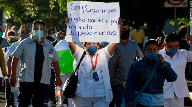 A health worker hold a sign reading,