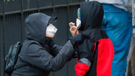 A woman adjusts her child's mask as they wait in line to be screened for Covid-19 in New York.