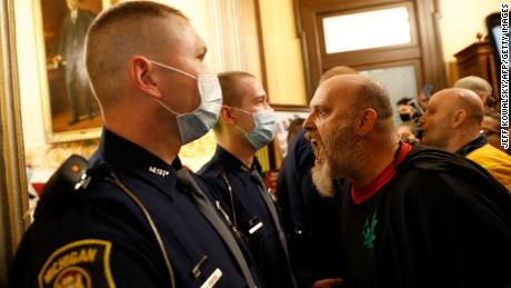Unmasked protesters in Michigan try to enter the state's House of Representatives chamber but are blocked by masked Michigan State Police.