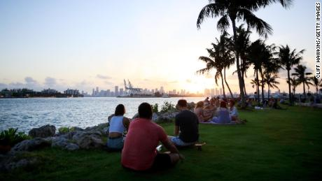 People gather for sunset at South Pointe Park on April 29, 2020 in Miami Beach, Florida.