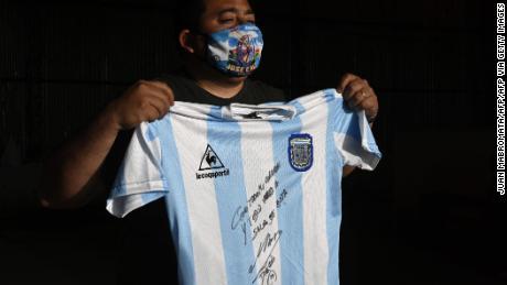 Un uomo tiene una replica dell'Argentina's squadra di calcio jersey utilizzato durante la finale di Coppa del Mondo del 1986 e firmato da Diego armando Maradona.