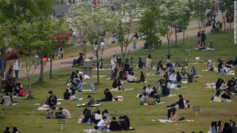 People sit in a park in Seoul, South Korea on Sunday. The country announced its highest number of new coronavirus cases for more than a month on Monday.