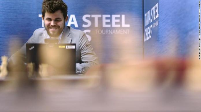 Carlsen speaks on his computer in a press room.
