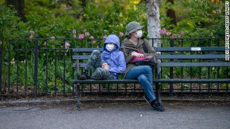 NEW YORK, NEW YORK - MAY 10: A mother and child wearing masks sit on a bench in Central Park amid the coronavirus pandemic on May 10, 2020 in New York City. COVID-19 has spread to most countries around the world, claiming over 283,000 lives with over 4.1 million cases. (Photo by Alexi Rosenfeld/Getty Images)