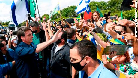 Brazil's President Jair Bolsonaro greets supporters upon arrival at Planalto Palace in Brasilia, on May 24.