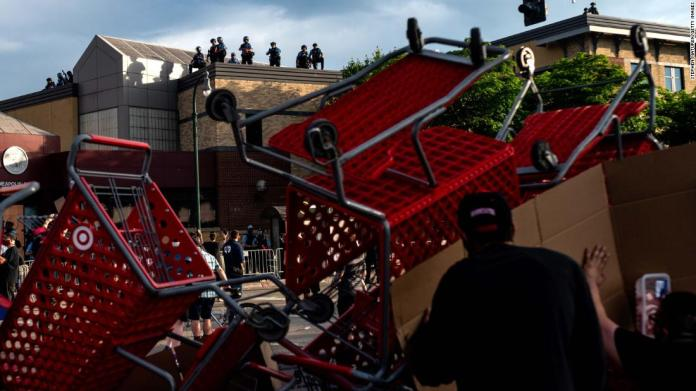 Protesters use shopping carts as a barricade as they confront police near a Minneapolis police precinct on May 27.