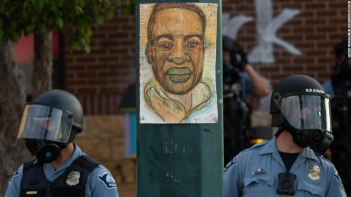 Minneapolis police stand by an illustration of Floyd as demonstrators rally on May 27.
