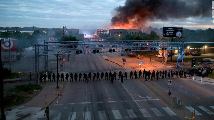 Police gather along Minneapolis' Lake Street early on May 29 as fires burned after a night of unrest.