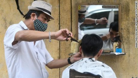 A roadside barber donning a face mask gives a haircut to a customer in Hanoi.