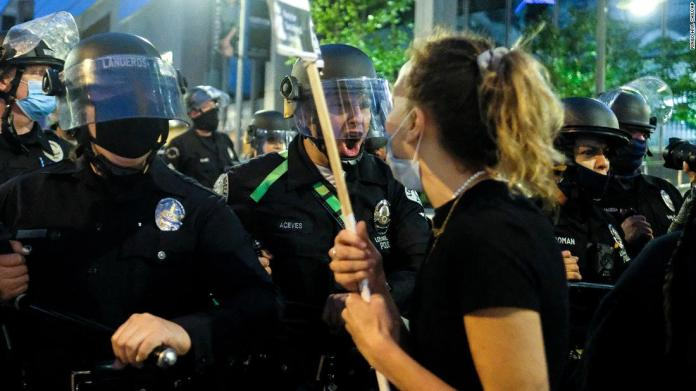 Police officers move forward to clear a street during a protest in downtown Los Angeles on May 29.