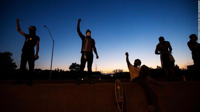 Men raise their fists after making their way onto Interstate 75 and stopping traffic in Cincinnati on May 29.