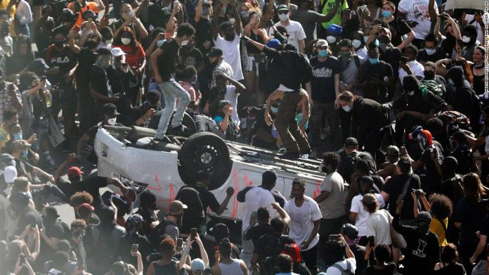 Protesters jump on an overturned car near the Municipal Services Building in Philadelphia on May 30.