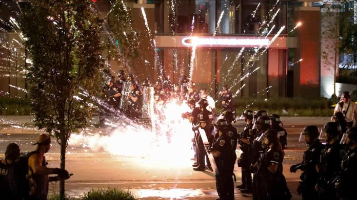 A firework explodes by a police line near the White House on May 30.