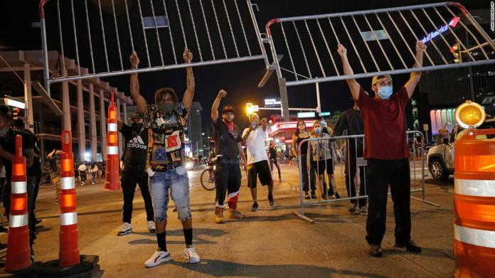 Protesters hold up metal gates as they build a barrier on a Las Vegas roadway on May 30.