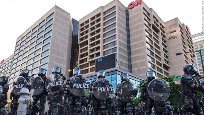 Police stand guard near the CNN Center and Centennial Olympic Park as protests continued in Atlanta on May 30.