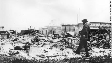 An African-American man with a camera staring at an iron bed frame soaring above the ash of a burning beam after the Tulsa Race Riots, 1921.