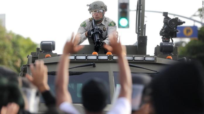 A police officer aims a nonlethal weapon as protesters raise their hands in Santa Monica, California, on May 31.