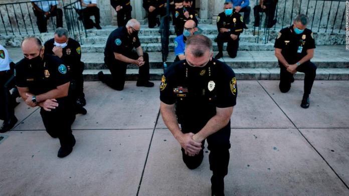 Police officers kneel during a rally in Coral Gables, Florida on May 30,.
