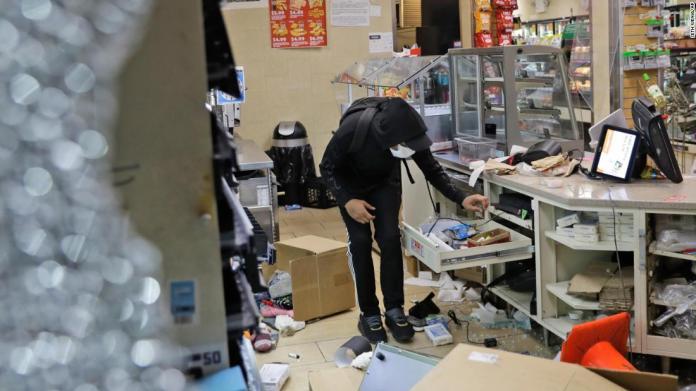 A person is seen inside a damaged 7-Eleven store in New York on May 31.