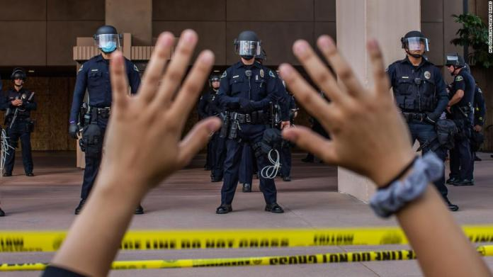 A demonstrator holds her hands up while she kneels in front of police officers at City Hall in Anaheim, California, on June 1.
