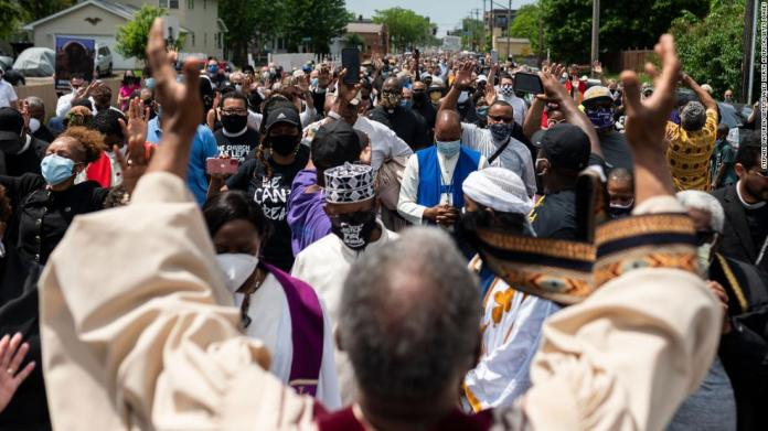 A group of clergy members stops and prays during a march to a George Floyd memorial in Minneapolis on June 2.