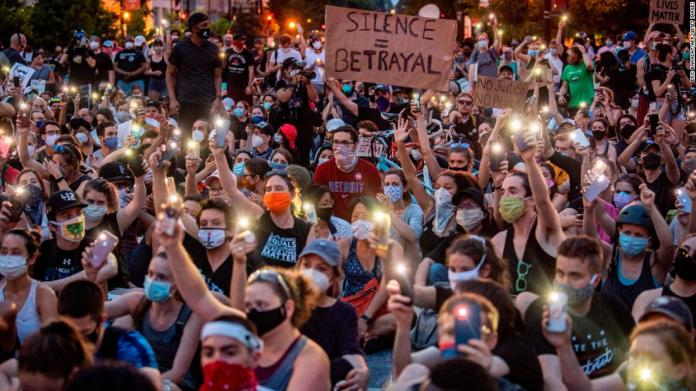Protesters hold up their phones during a demonstration outside the White House on June 3.
