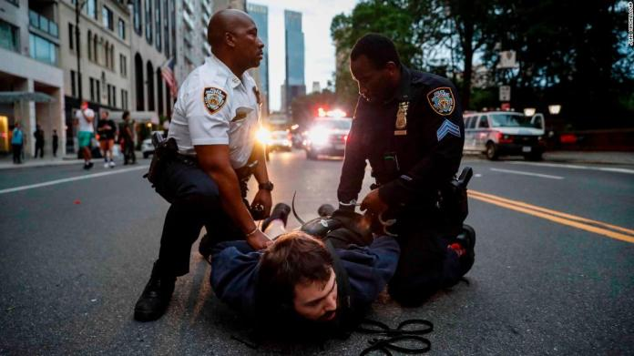 A protester is arrested for violating curfew near the Plaza Hotel in New York on June 3.