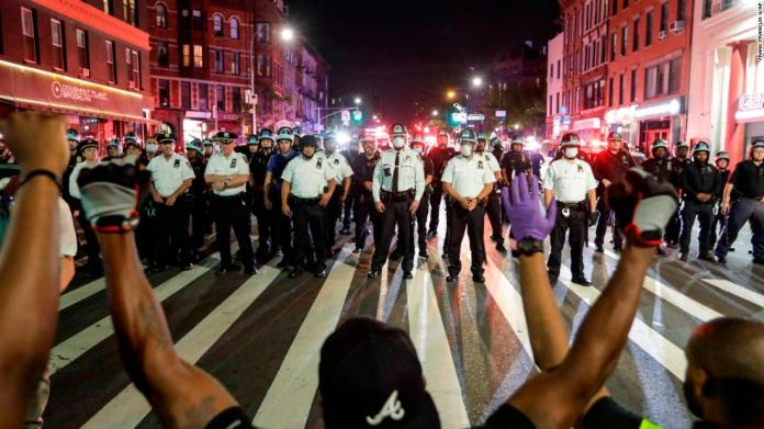 Protesters take a knee in front of a line of police officers in Brooklyn, New York, on June 4.