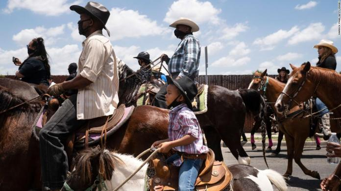 "A young boy rides with the Compton Cowboys during a ""peace ride"" for George Floyd in Compton, California, on June 7."