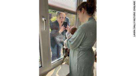 Женщина впервые встречает своего внука через закрытое окно во время блокировки в Ливерпуле, Англия