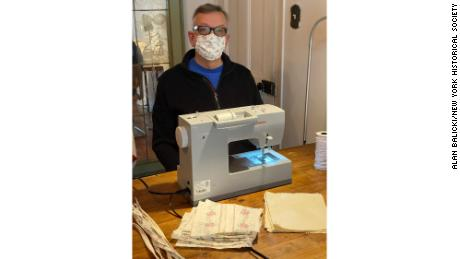 Мужчина использует швейную машину для создания самодельных масок для лица во время блокировки в Нью-Йорке