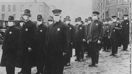 Полицейские в Сиэтле носят защитные марлевые маски во время эпидемии гриппа 1918 года, унесшей миллионы жизней по всему миру