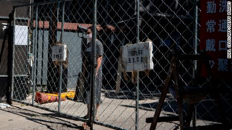 A woman stands behind a fence as she waits for the delivery of goods she ordered online in a residential area under lockdown near the closed Xinfadi market in Beijing.