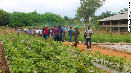 Father Godfrey Nzamujo educates a group of people on his zero waste farm in Benin.
