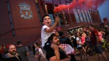 Fans celebrate Liverpool winning the championship title of the English Premier League following Chelsea's 2-1 victory over Manchester City, outside  Anfield stadium in Liverpool, north west England on june 25, 2020. - Liverpool were crowned Premier League champions without kicking a ball on Thursday as Chelsea's 2-1 win over Manchester City ended the Reds' 30-year wait to win the English title. (Photo by Oli SCARFF / AFP) (Photo by OLI SCARFF/AFP via Getty Images)