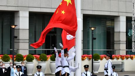 The Chinese (front) and Hong Kong flags are released during a flag-raising ceremony to mark China's National Day celebrations early morning in Hong Kong on July 1, 2020.