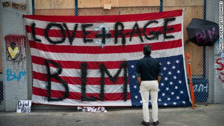 A man views an upside down US flag at the Seattle Police Department's vacated East Precinct on June 14 in the CHOP.