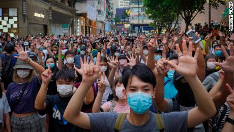 Protesters hold up five fingers in Hong Kong to signal their five lawsuits against the new national security law on July 1, 2020.