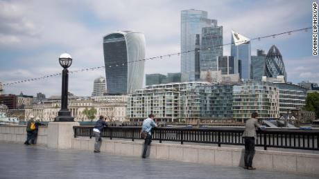 People observe social distancing as they look out at the skyline of London's financial district on June 9.